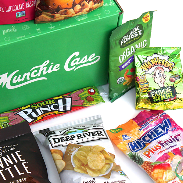 mix of snacks laying in front of green munchie case subscription box