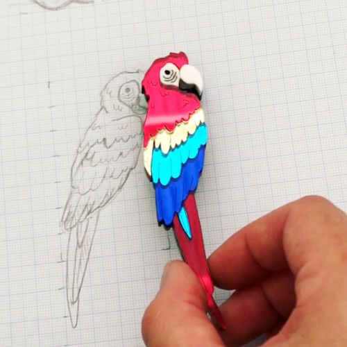 sketch of a bird on graph paper, next to the final laser cut brooch
