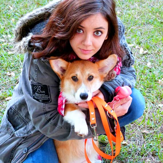 girl holding dog with harness