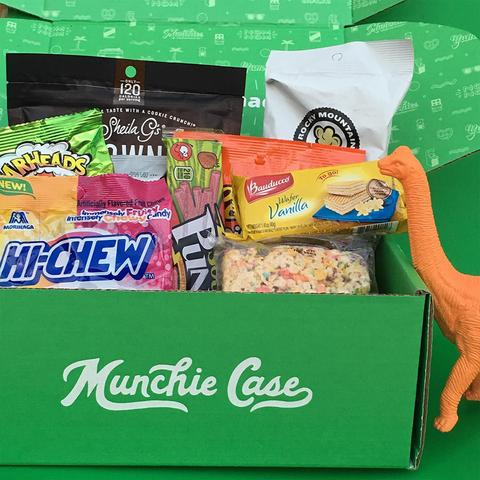 orange toy dinosaur looking a mix of snacks in a green munchie case