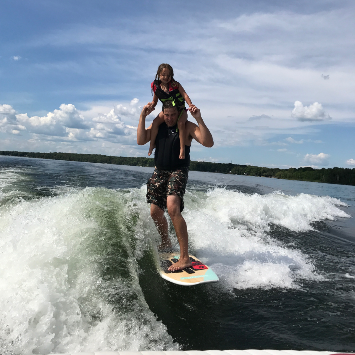 Kids wakesurfing on shoulders with dad