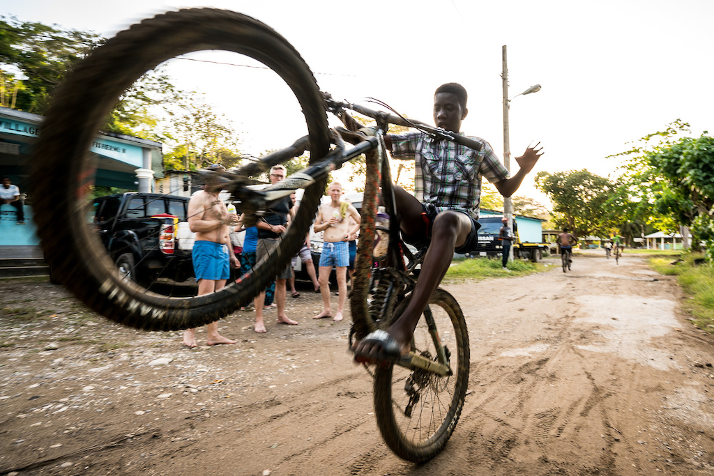 boy in Jamaica popping a wheelie on a bike