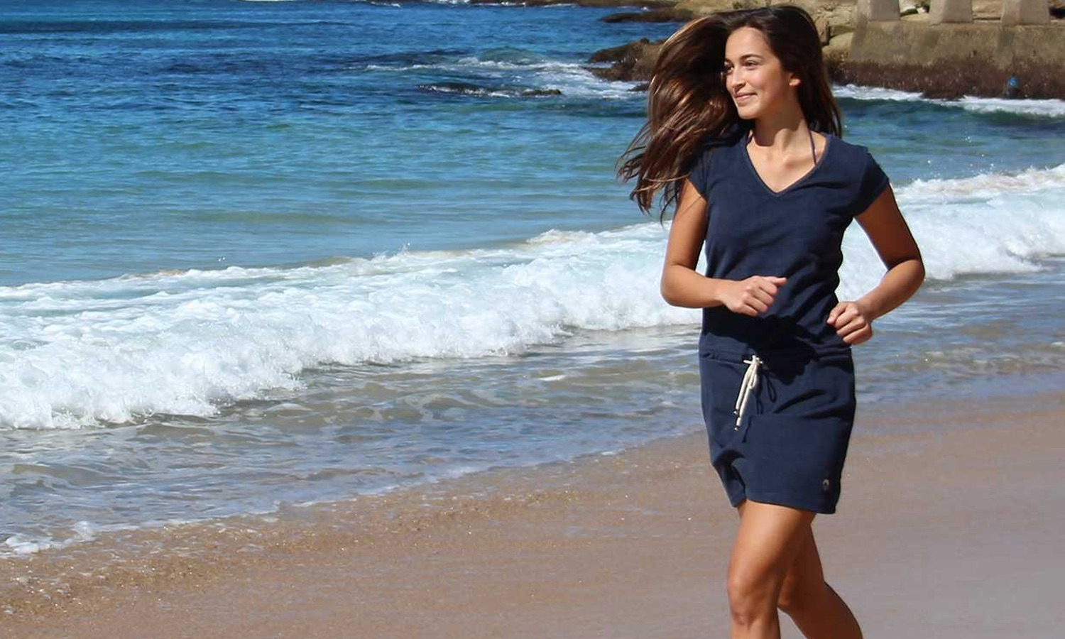 woman running on the beach with a blue dress
