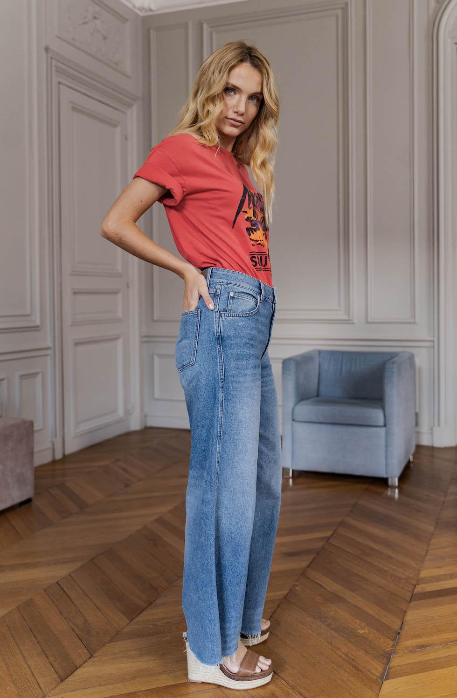 Femme qui porte un jean de la marque parisienne NVY d'un style été Miami.