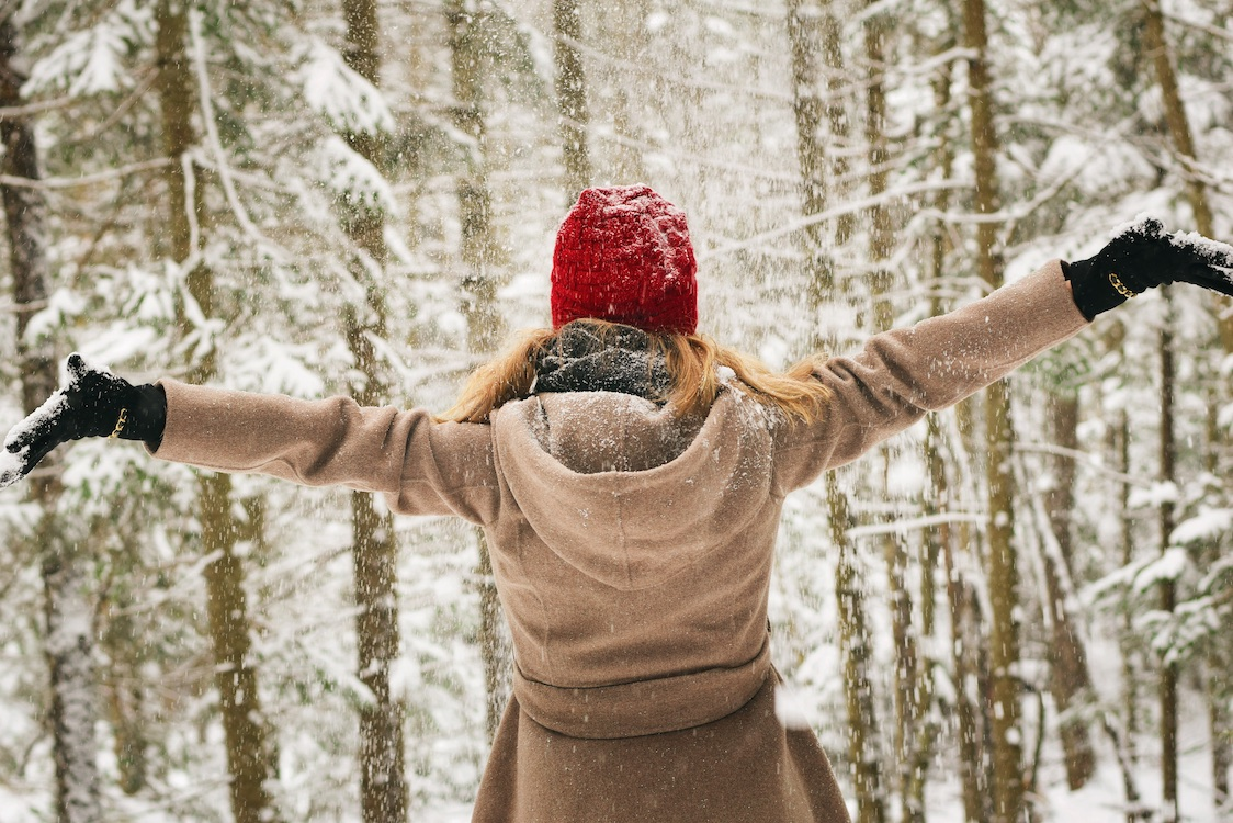 A woman in a jacket and red hat faces away from the camera with her arms in the air, facing a forest in winter.
